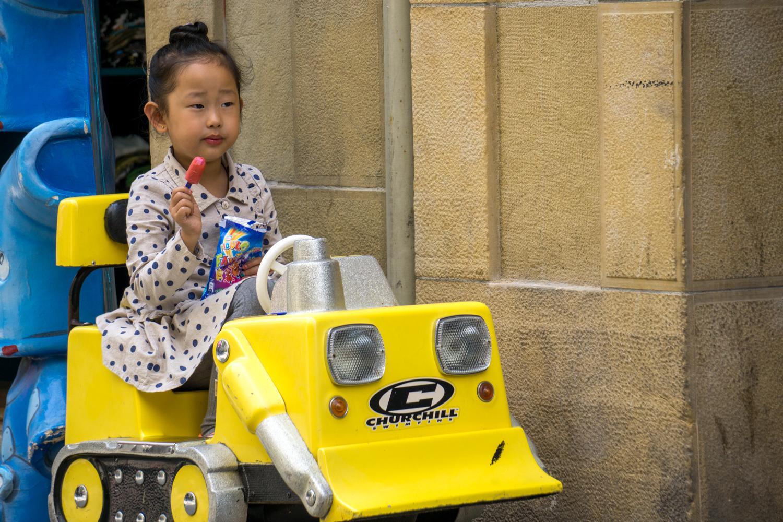 A young girl enjoys a snack and a drive in San Sebastián.